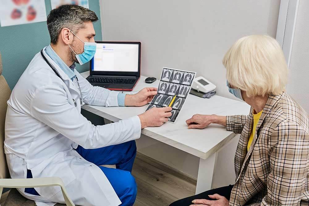 Doctor explica a mujer mayor las secuelas de la fibrosis quística en sus pulmones en una radiografía.