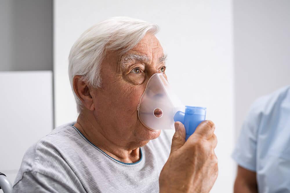 Anciano inhala oxígeno con un oxigenador que lleva en la mano.