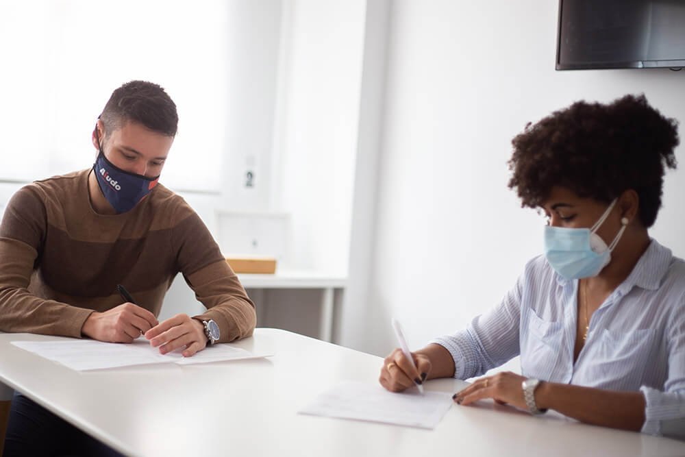 Daniel Ibiza formalizando un contrato con una cuidadora. Están sentados en una mesa.