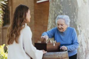Abuela y cuidadora jugando al ajedrez en el parque ribalta