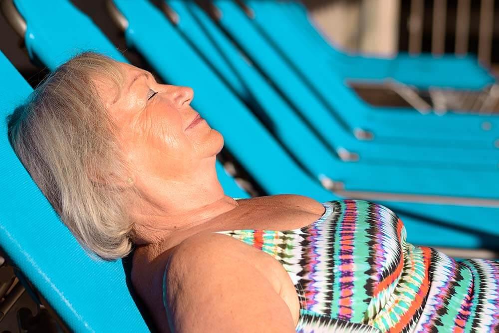 Mujer mayor tomando el sol en una tumbona en la piscina.