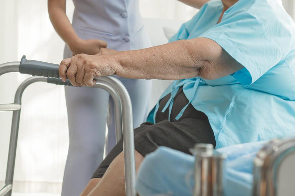 Cuidadora ayuda a levantarse a anciana con ayuda de andador.