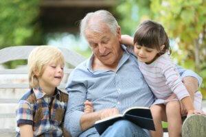 Abuelo leyendo un libro con sus nietos