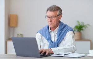 Persona mayor con un ordenador emprendiendo
