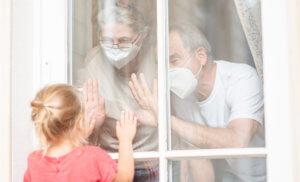 Abuelos con mascarilla saludando a su nieta tras la ventana