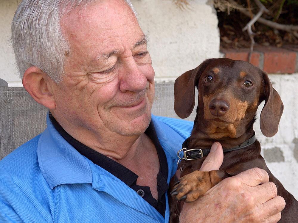 Foto de un anciano feliz con un perro salchicha en sus brazos.