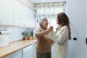 Abuela y cuidadora bailando canciones de cuando la abuela era joven