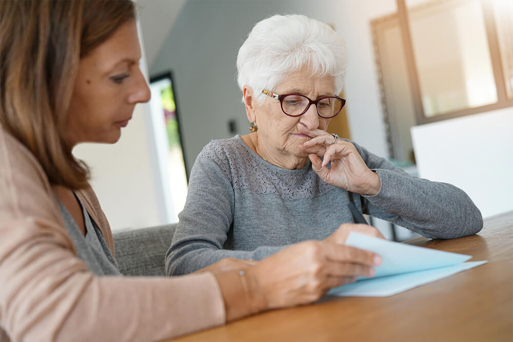 Anciana y cuidadora sentadas frente a una mesa mirando unos papeles.