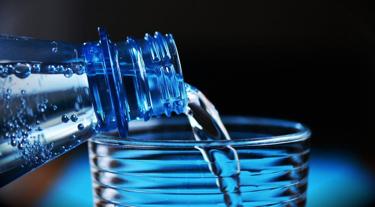 Primer plano de botella de agua derramando agua dentro de un vaso.