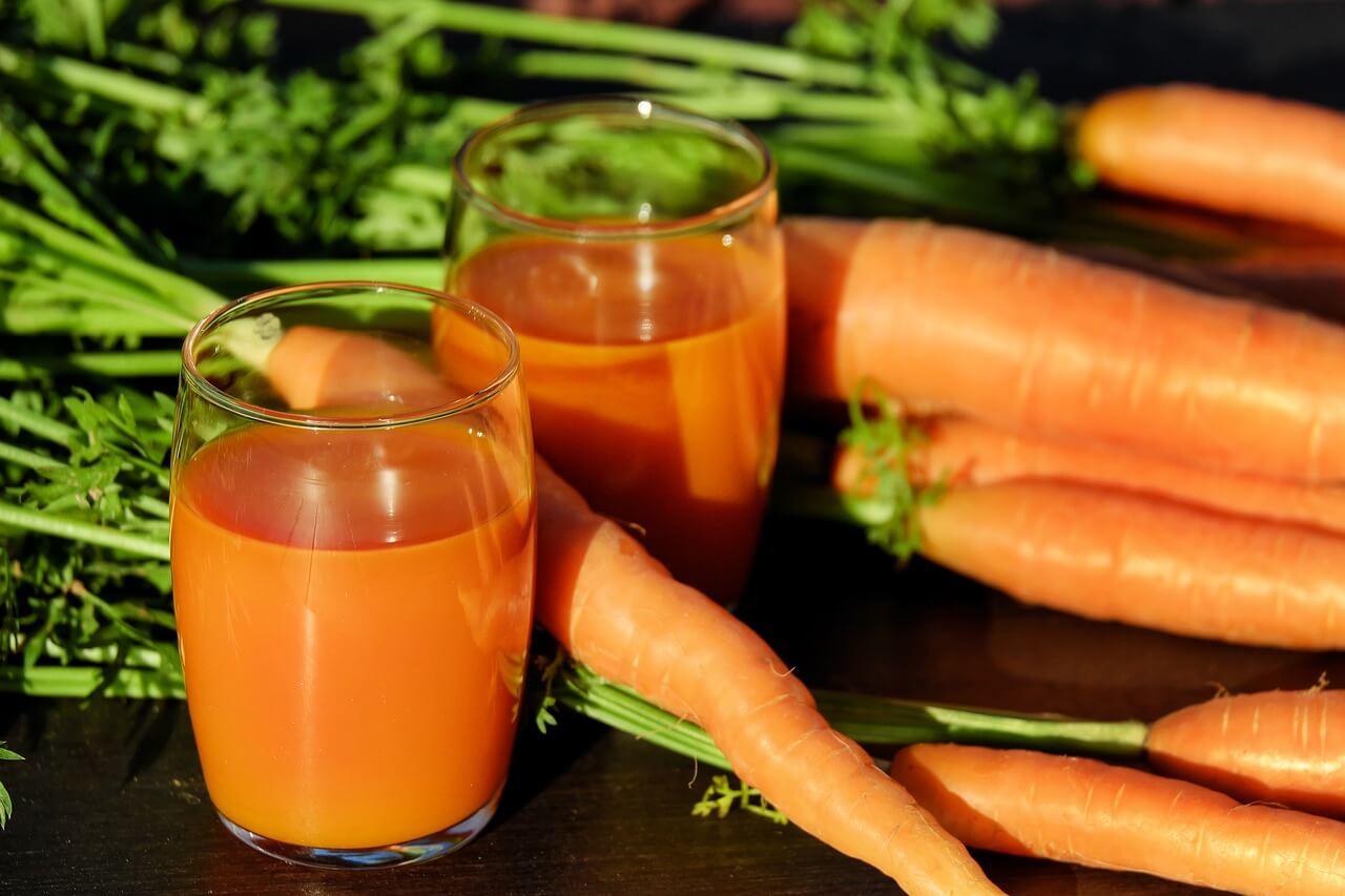 Puñado de zanahorias junto a dos vasos de licuado de zanahoria.