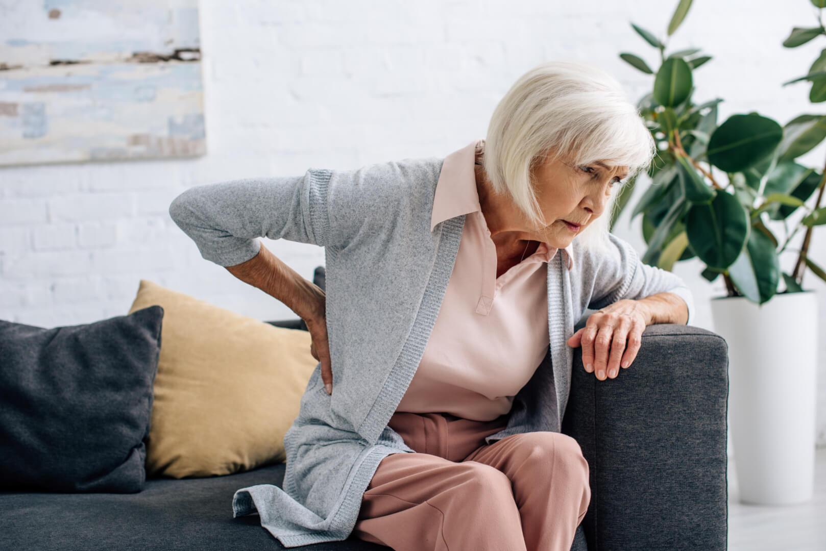 Mujer anciana con dolor de espalda causado por la osteoporosis